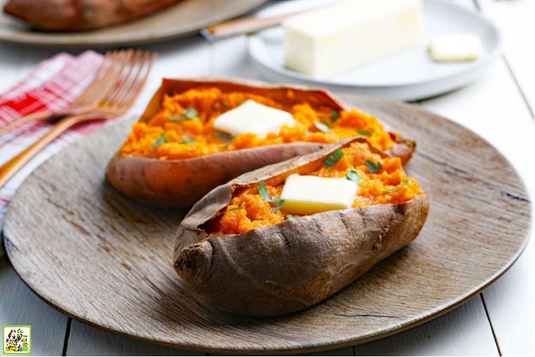 A brown plate with two Instant Pot Sweet Potatoes with pats of butter, forks, and napkins.