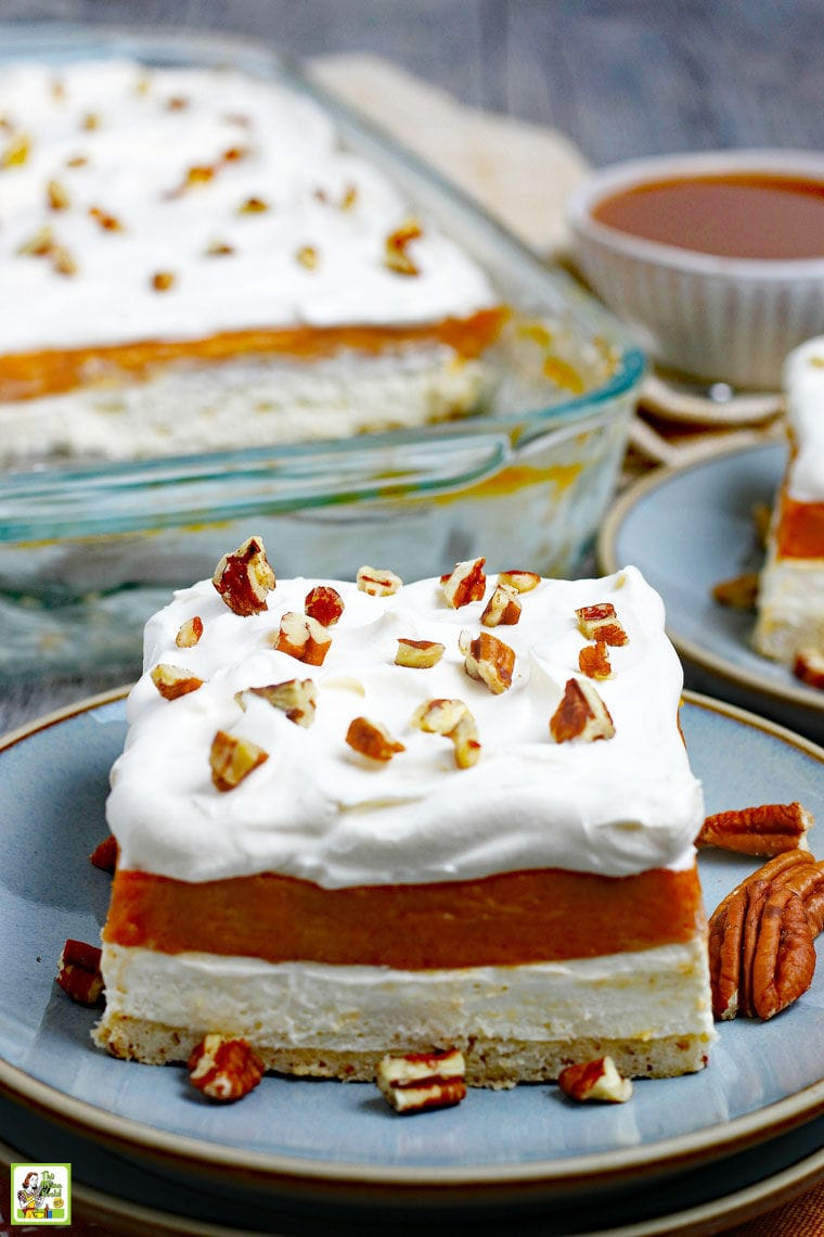 A large serving of Pumpkin Cheesecake Lasagna dessert on a blue plate with pecans.