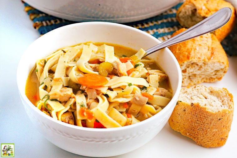 A bowl of Leftover Turkey Soup with spoon and pieces of crusty French bread.