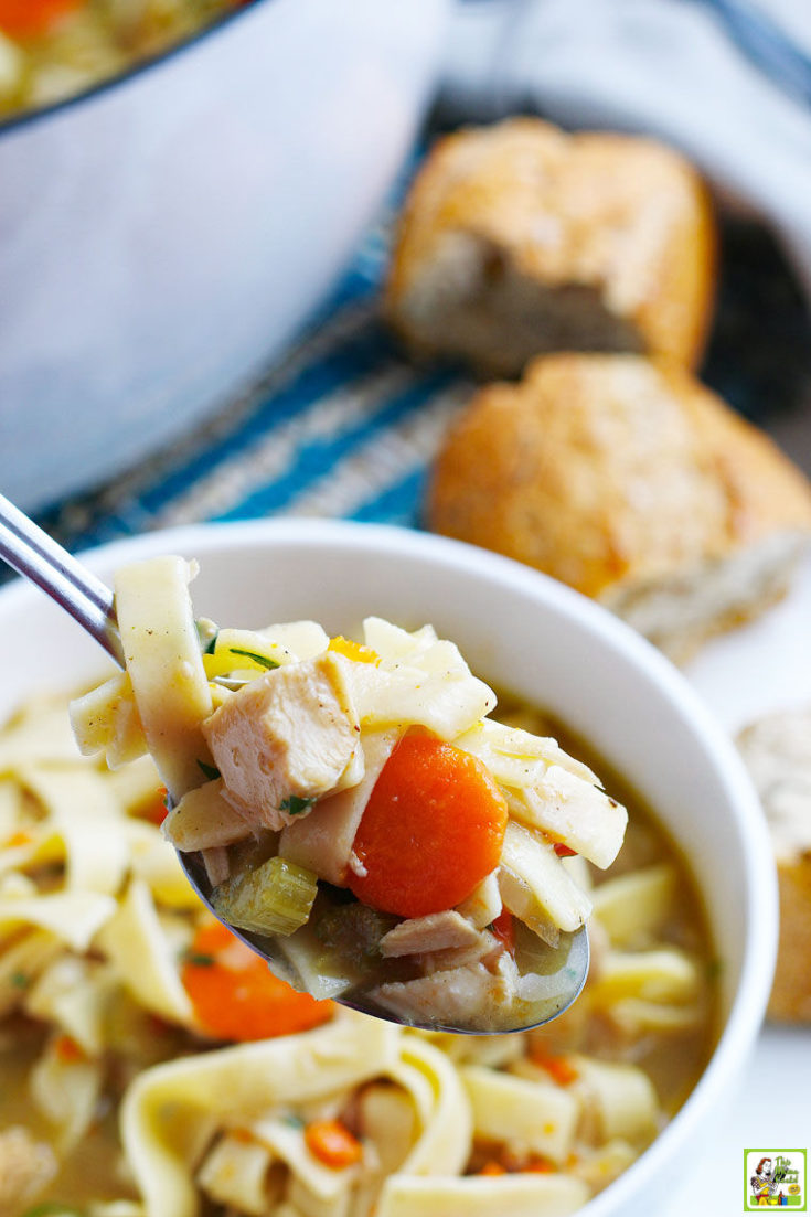 A spoon and bowl of Turkey Soup with bread and a Dutch oven stock pot in the background.