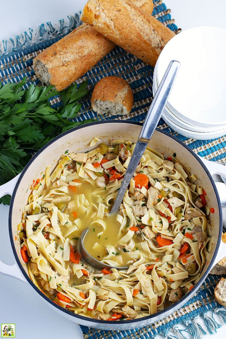 Overhead shot of a pot of turkey noodle soup with a ladle, soup bowls, and French bread, on a blue placemat.