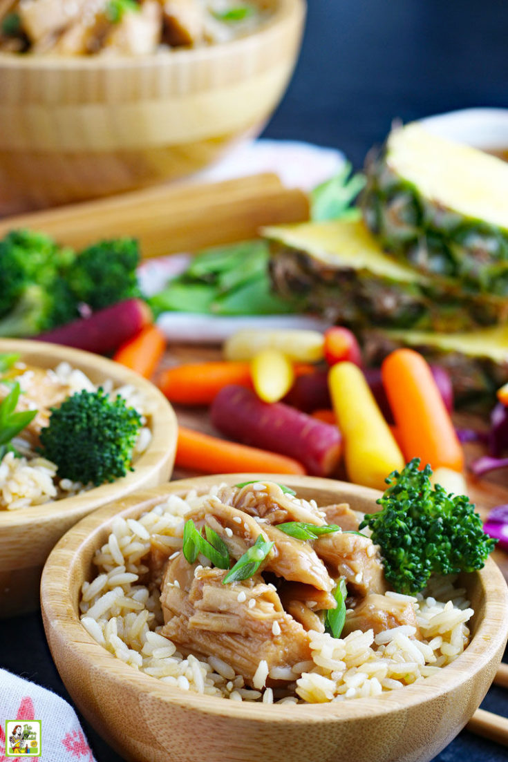 Serving bowls of teriyaki chicken with rice and broccoli with vegetables in the background.