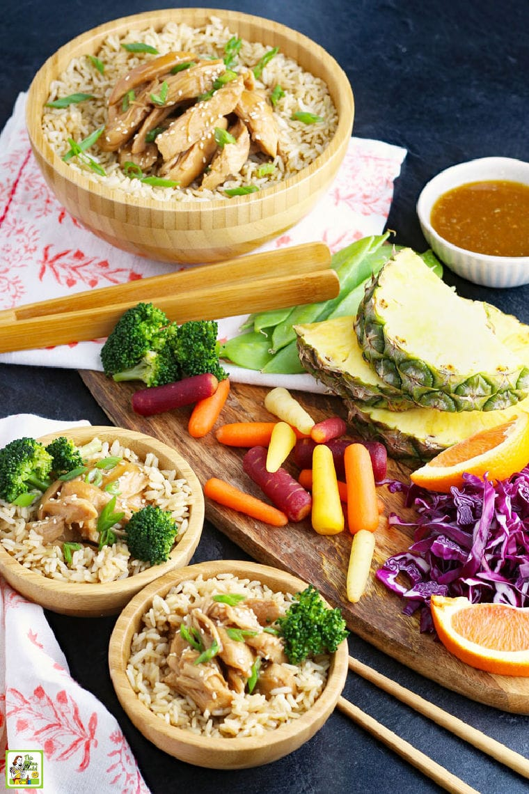 Teriyaki chicken with rice and broccoli in bowls with wooden serving utensils, vegetables, and fruits, colorful napkins, and a bowl of teriyaki sauce.