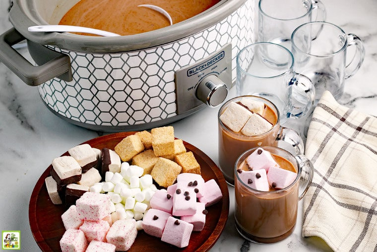 Crockpot Hot Chocolate made in a slow cooker served with marshmallows in glass mugs.