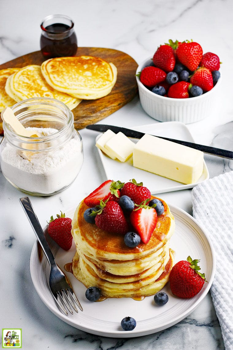 A stack of pancakes with fruit on a white plate with pancake mix in a glass jar, a stick of butter, more pancakes, and a bowl of fruit in the background.