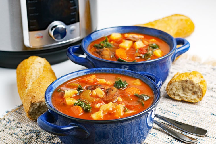 Two blue bowls of Instant Pot Vegetable Soup with crunchy French bread and spoons on a knit placemat with a pressure cooker in the background.