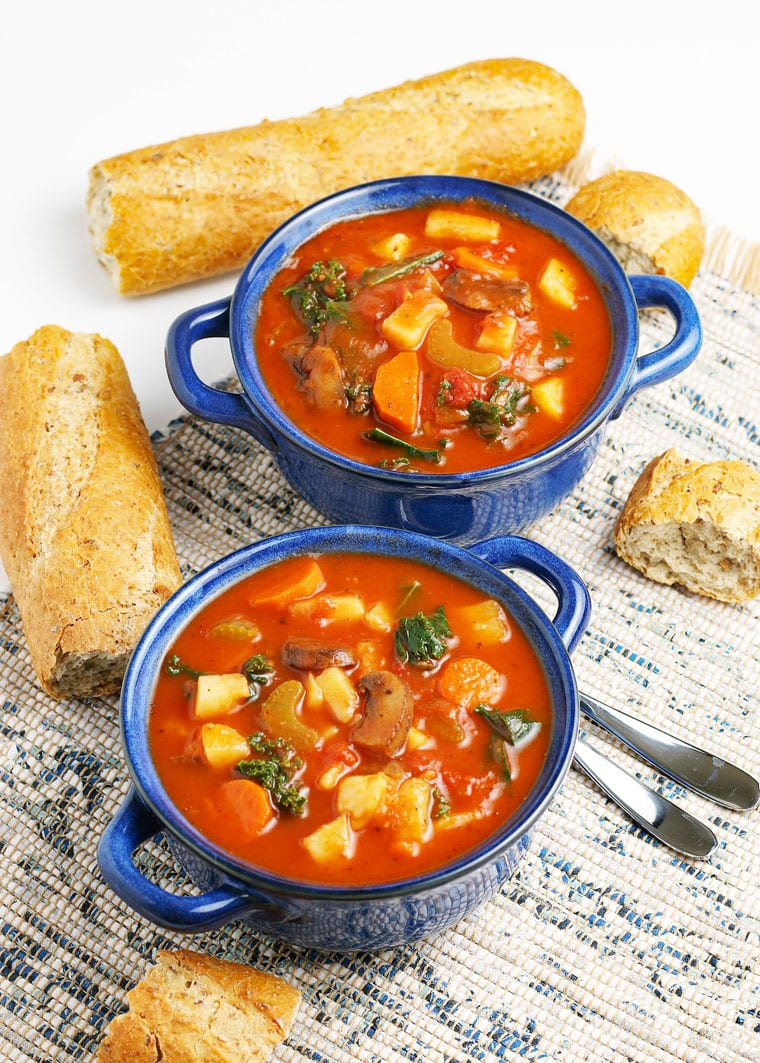 Two lug blue bowls of vegetable soup with French bread and spoons.
