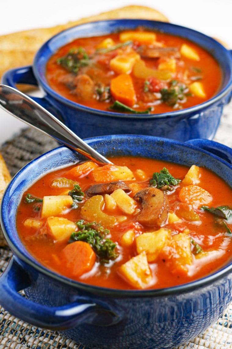 Close up of a blue bowls of vegetable soup with soup spoon.