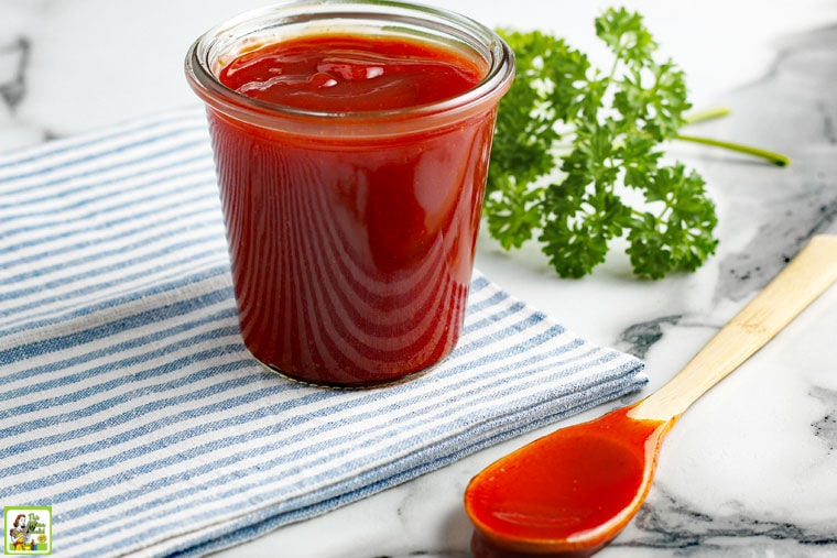 Sugar Free BBQ Sauce in a glass jar with a serving spoon, napkin and parsley.
