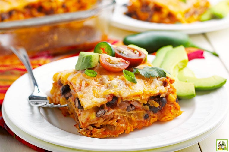 A plate of Chicken Enchilada Casserole with slices of avocados and a fork with a casserole and more plates in the background.