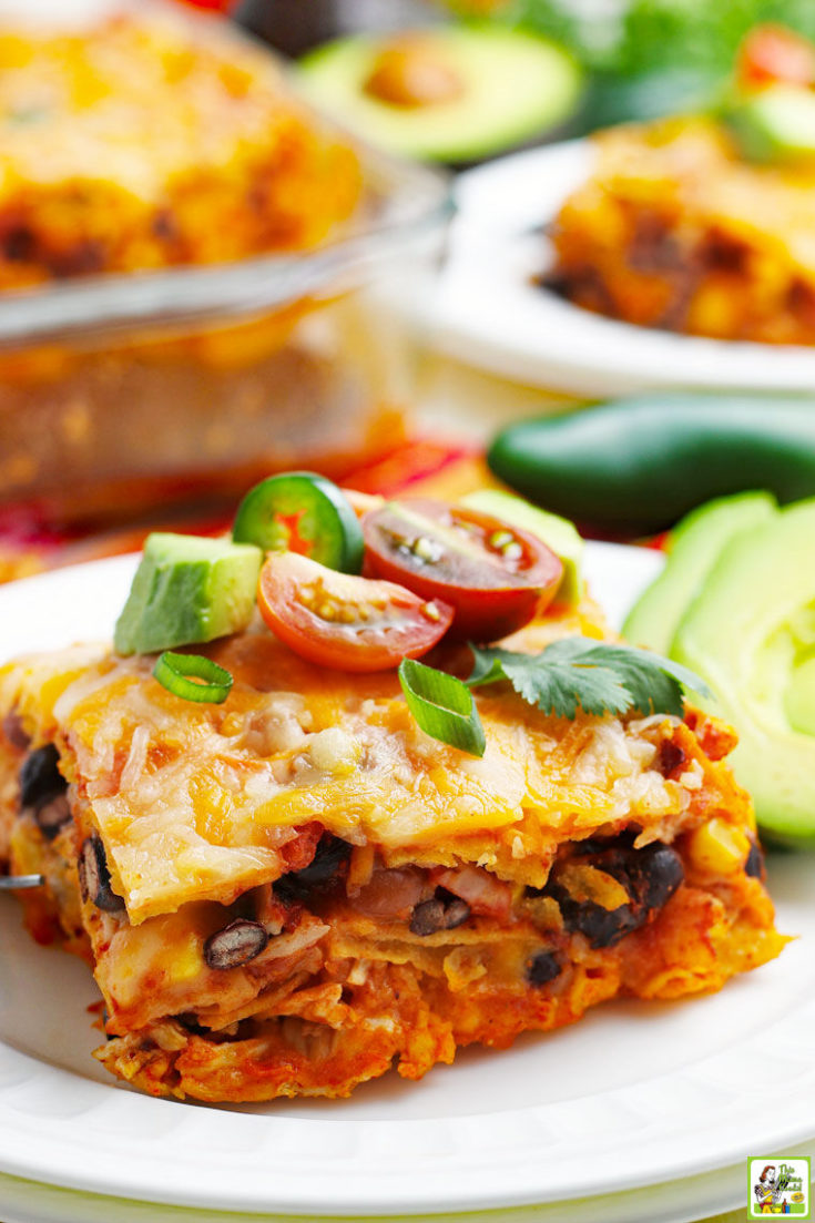 Close up of a slice of chicken enchilada casserole on a white plate with avocado and tomatoes.