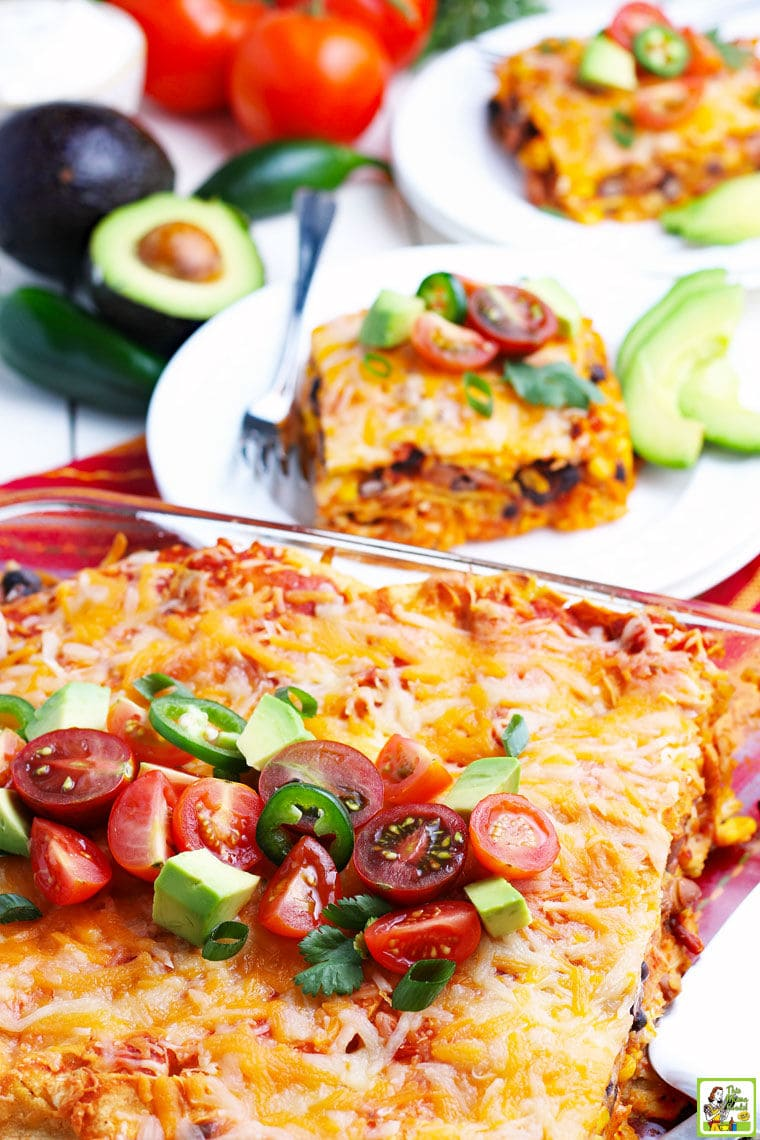 A glass casserole dish of enchiladas with avocados, tomatoes, plates of chicken enchiladas, and festive striped napkins.