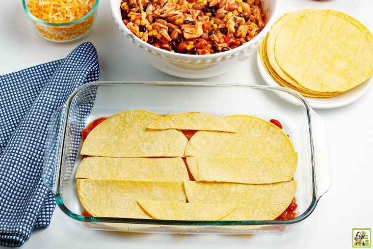 Corn tortillas layed on the bottom of a prepared baking dish.