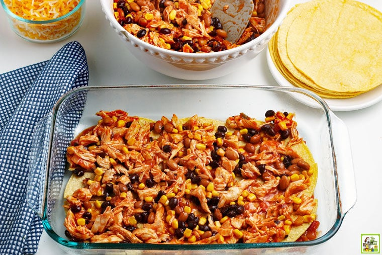 Layer of beans and chicken mixture on top of corn tortillas in a glass baking dish.