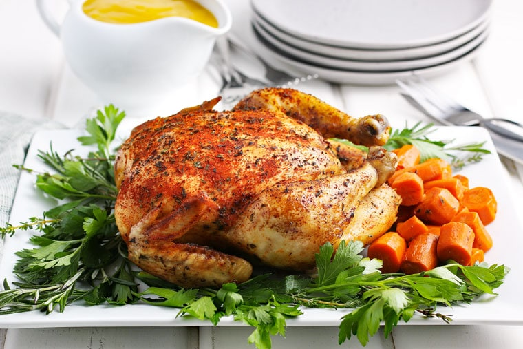 A Crockpot Whole Chicken on a white platter with herbs and carrots with gravy boat, plates and utensils.
