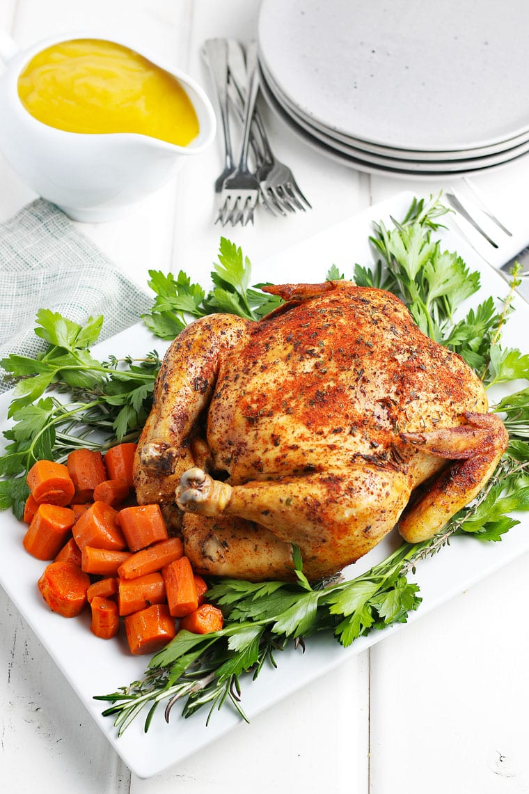 A crockpot whole chicken on a platter with carrots and parsley.