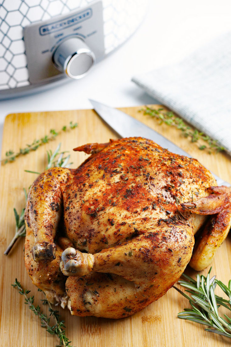 A roasted crockpot whole chicken on a wooden cutting board with a knife.