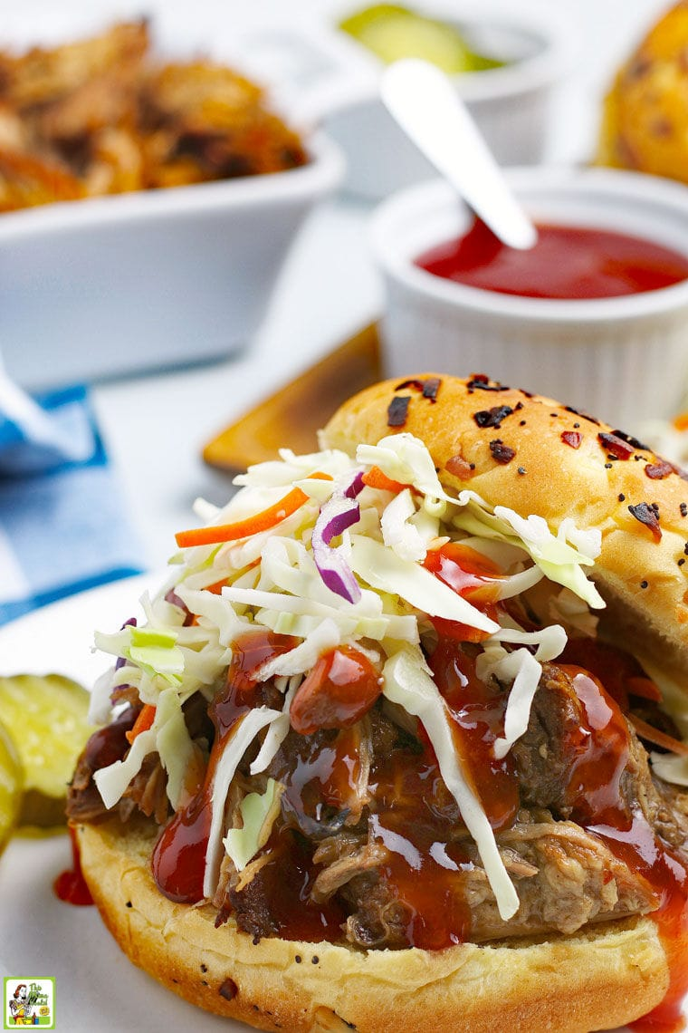 A BBQ pulled pork sandwich with coleslaw and pickles and a small jar of BBQ sauce.