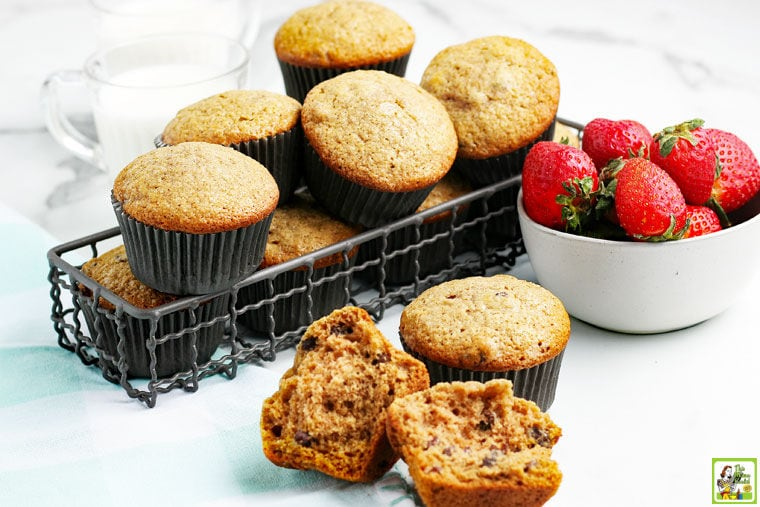 Gluten free applesauce muffins on a tabletop and in a wire basket with a bowl of strawberries.