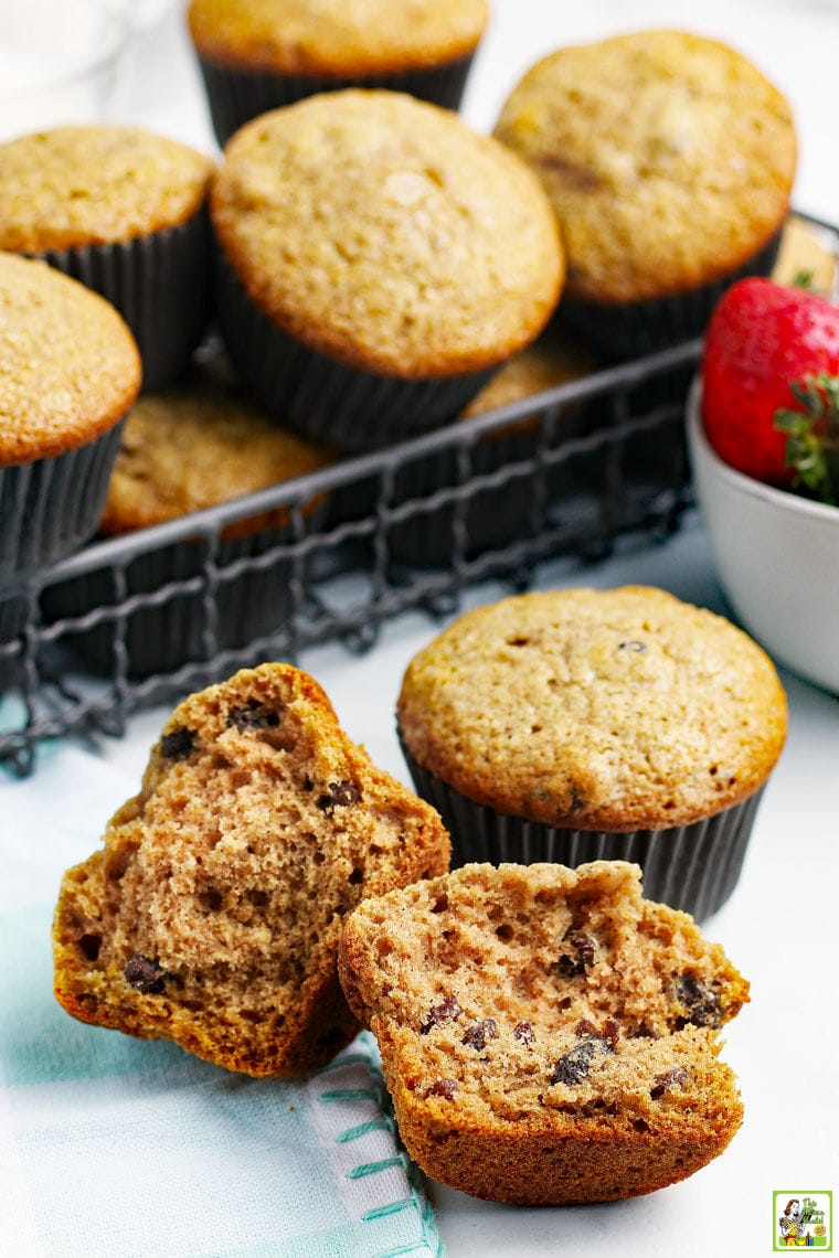 A wire basket of applesauce muffins with a broken muffin in front and a bowl of fresh strawberries with a blue and white tea towel.