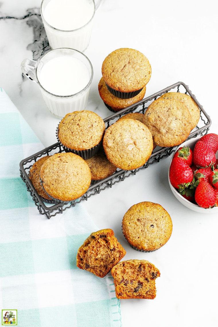 Muffins in a wire basket, two glasses of milk, a bowl of strawberries, and a blue and white napkin on a white countertop.