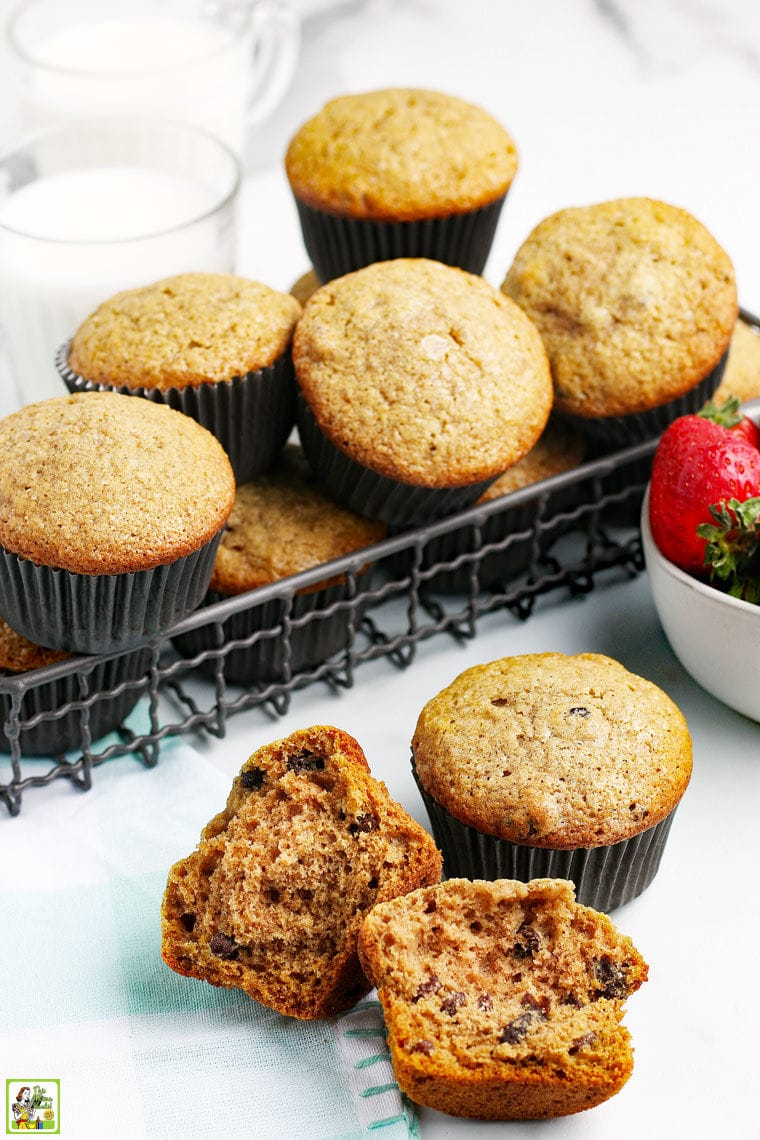 Closeup of a broken muffin and a basket of applesauce muffins with a bowl of strawberries.