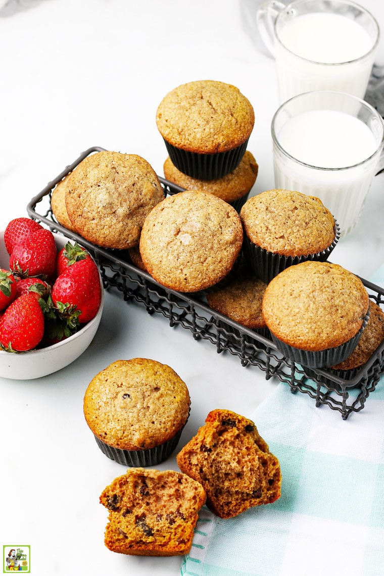 A bowl of strawberries, a basket of freshly baked muffins, a glass of milk, and a napkin on a white tabletop.