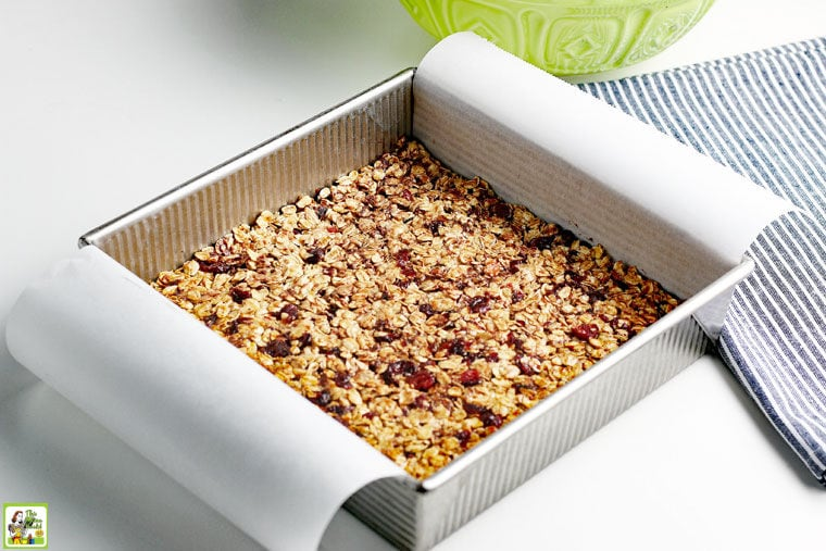 Baking homemade granola bars in a square pan with parchment paper hanging over the sides.