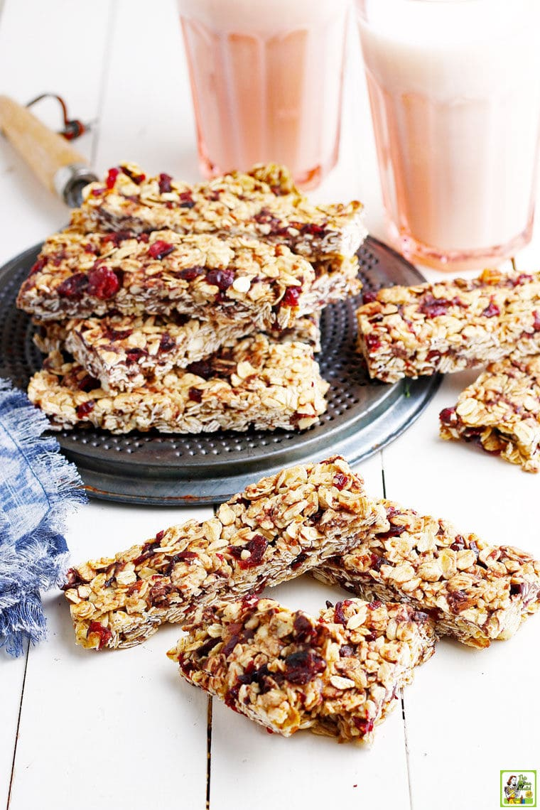 Stacks of homemade granola bars, a metal trivet, pink glasses of milk, a blue and white napkin, on a white wooden board.