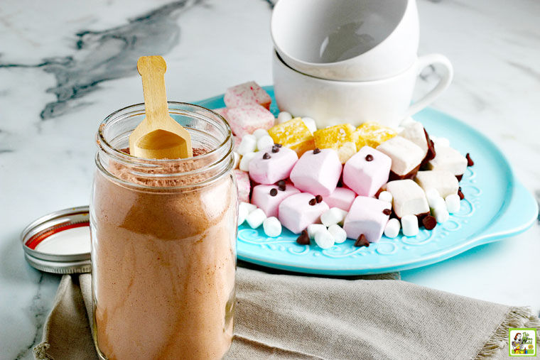A mason jar of Homemade Hot Chocolate Mix, napkins, mugs, and a plate of hot cocoa toppings like marshmalows and chocolate chips.