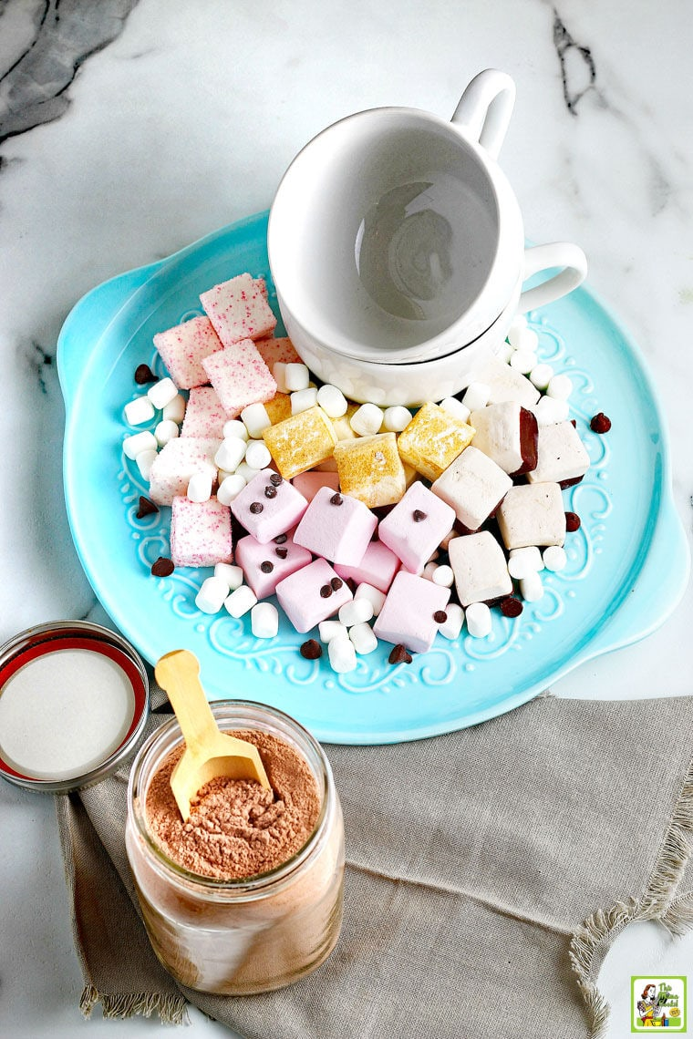 An overhead shot of a mason jar of hot chocolate mix with a wooden scoop and lid next to a blue plate of marshmallows, chocolate chips, and white ceramic mugs.