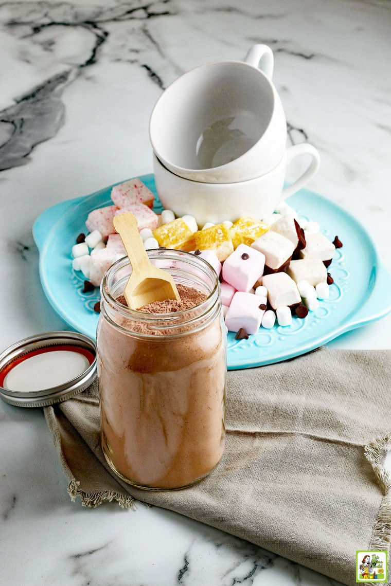 A large glass jar of hot chocolate mix with a wooden scoop and lid next to a blue plate of marshmallows, chocolate chips, and white ceramic mugs. on a marble table top with a gray napkin.