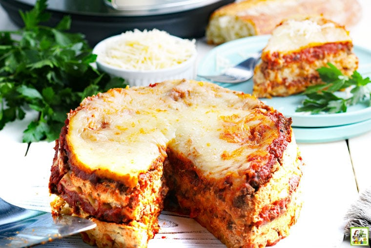 Instant Pot Lasagna with a slice cut out, with bowl of shredded cheese and a plate of lasagna in the background.