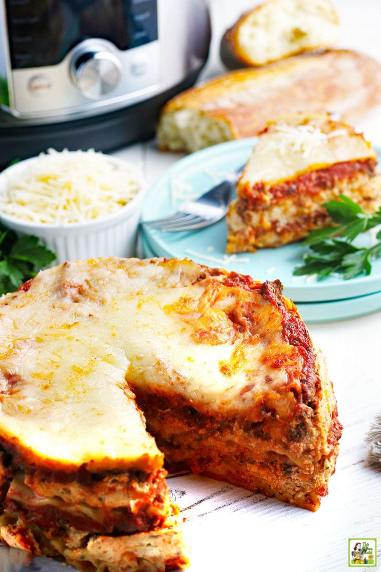Lasagna with a slice on a blue plate with a fork, bread, and a bowl of shredded cheese.
