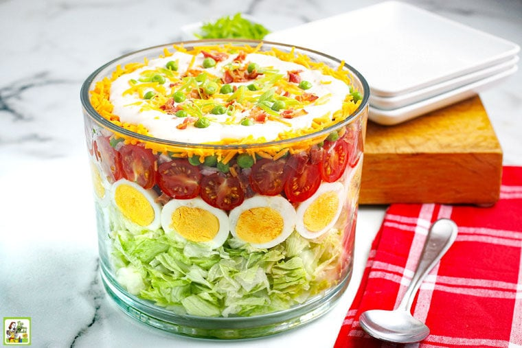 A glass trifle bowl of Seven Layer Salad with serving spoon, red napkin, white plates, and wooden cutting board.