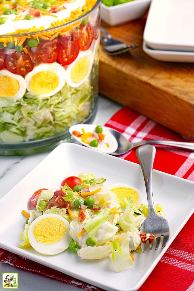 A white plate of Seven Layer Salad with fork, a red napkin, a big glass bowl of layered salad, a wood cutting board, and more white plates.