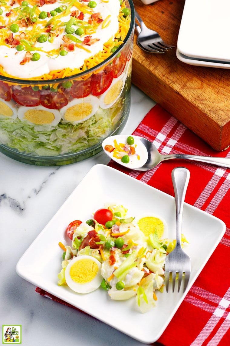 A plate of salad with fork and red napkin with a large glass bowl of layered salad in the background.