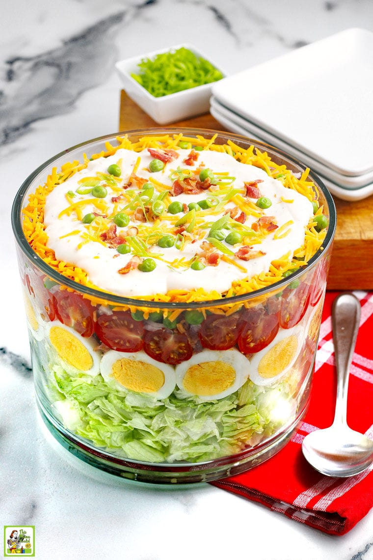 A large glass bowl with a layered salad filled with eggs, tomatoes, peas, cheese, onions, and dressing, plates, serving spoon, and wooden cutting board on a red napkin.