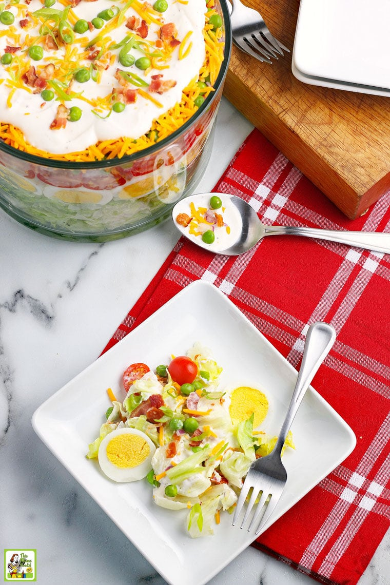 Overhead shot of a plate of salad with fork, red napkin. a large glass bowl of layered salad, a serving spoon, and a wooden cutting board.