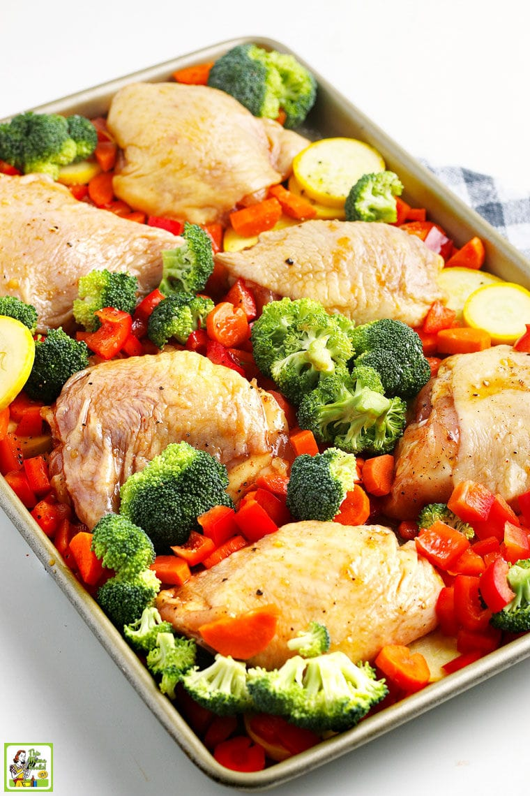 Marinated chicken skin on thighs and colorful chopped vegetables on a rimmed baking sheet.