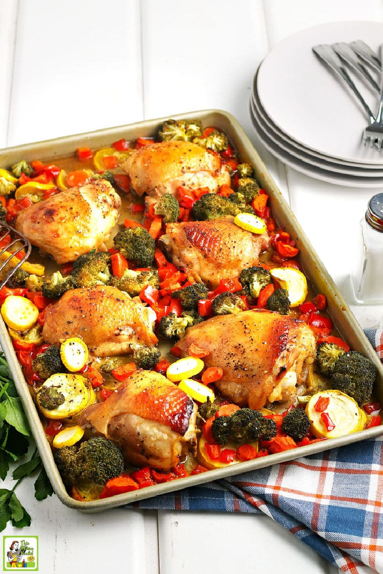 A roasting pan of cooked chicken thighs and vegetables with a colorful blue, orange and white napkin, white plates, and salt and pepper shakers.