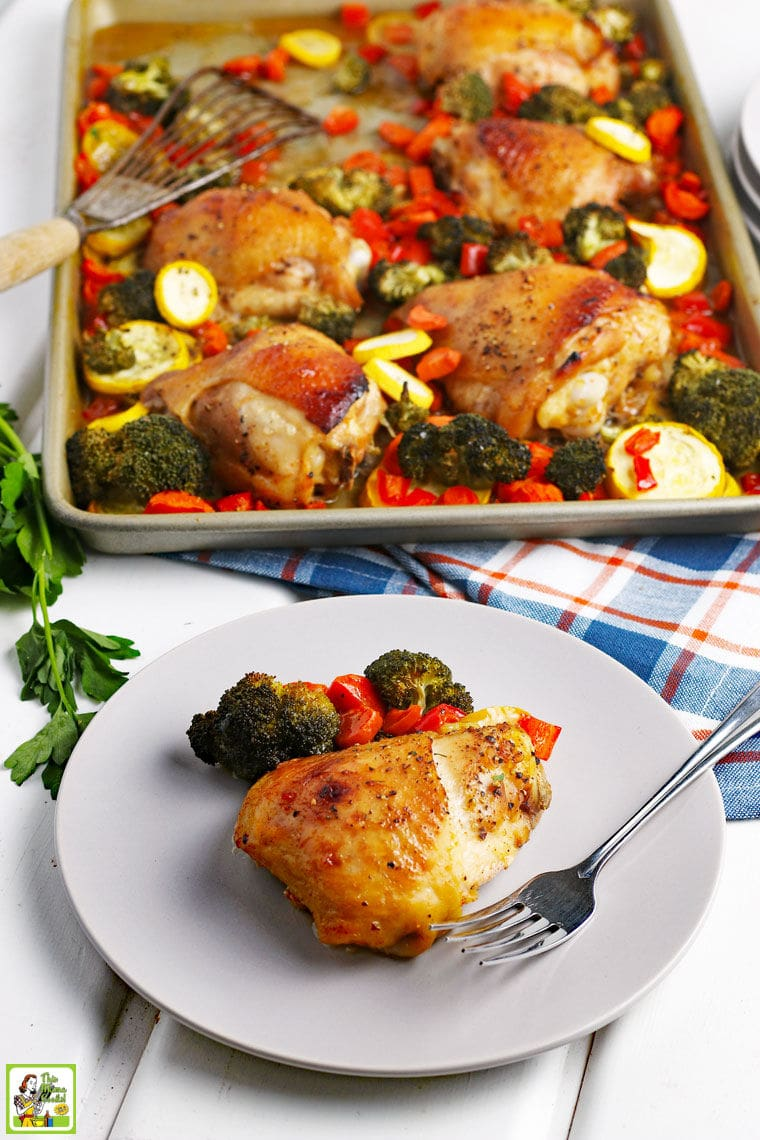 A plate of cooked chicken and vegetables with fork and napkin with a pan of baked chicken thighs and vegetables in the background.