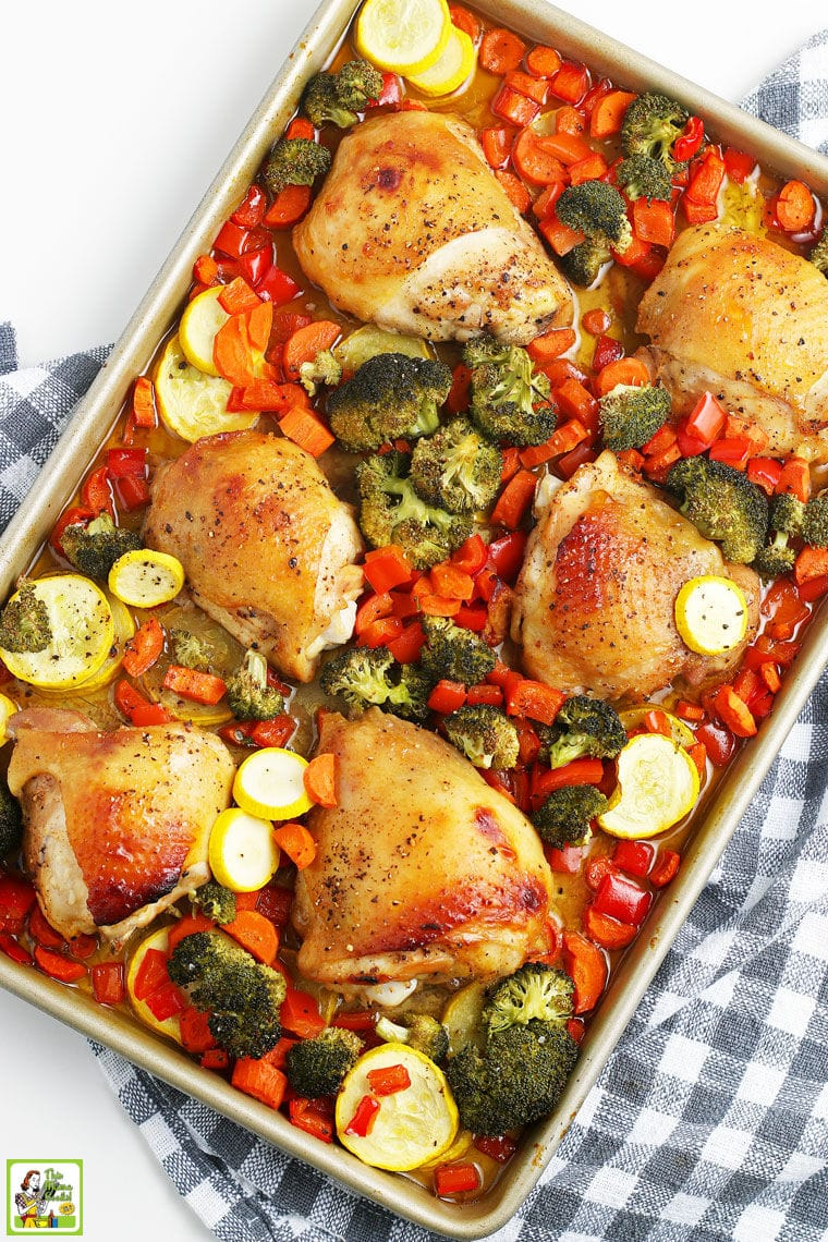 Overhead shot of roasted chicken thighs and chopped vegetables on a gray and white dish towel.
