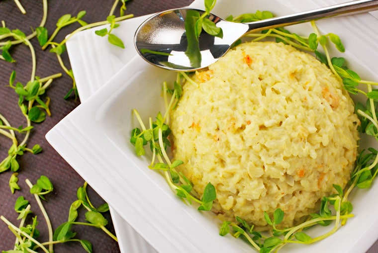 A bowl of Seafood Risotto with spoon and pea shoots.