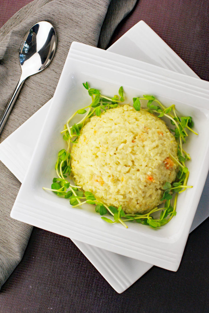 A scoop of seafood risotto in a white bowl on a plate with a silver spoon and gray napkin.