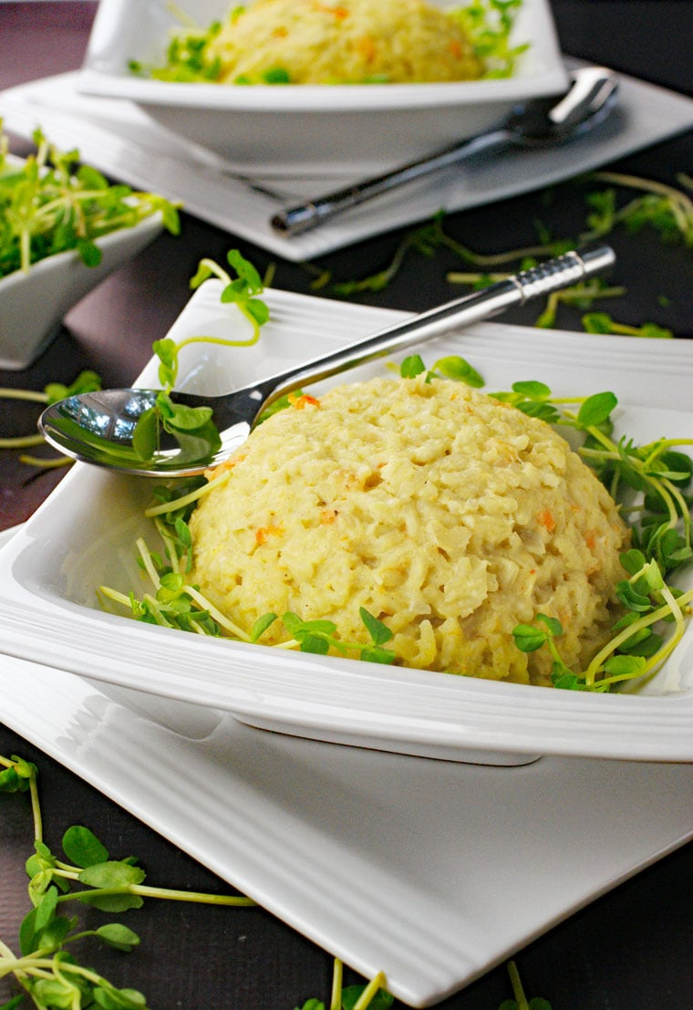White bowls of seafood risotto with silver spoons.