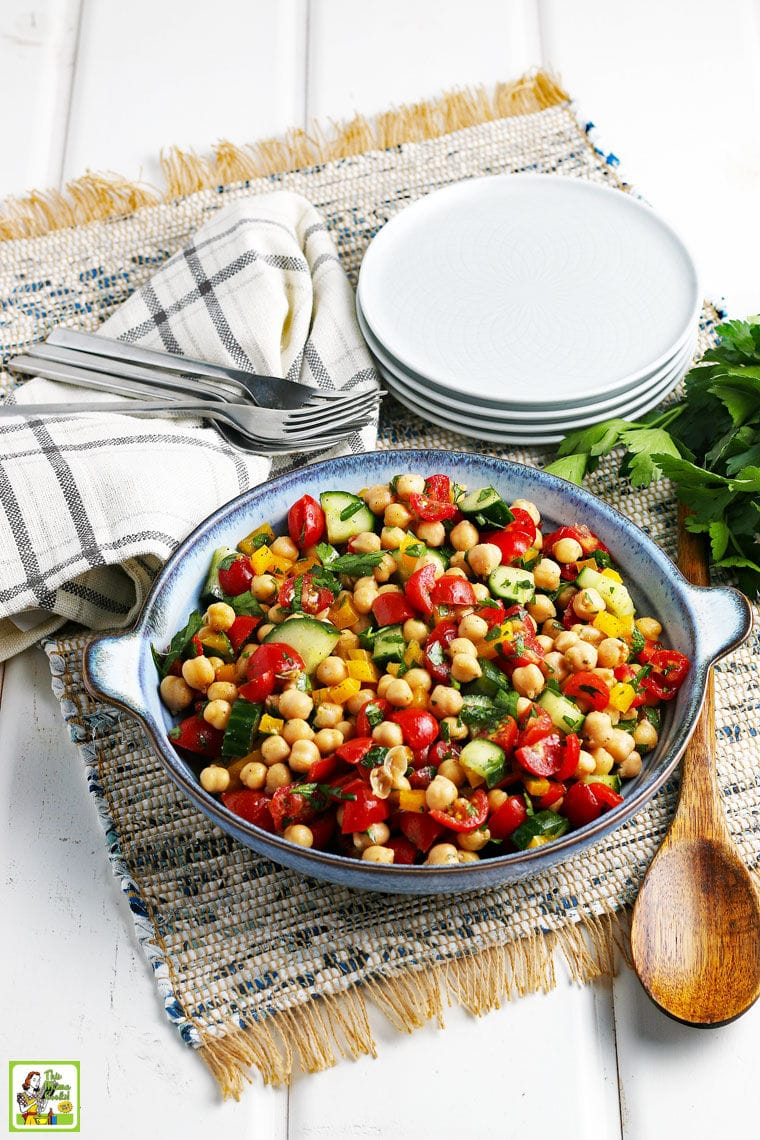 A bowl fo Garbanzo Bean Salad Recipe with a wooden spoon, white plates, forks, napkins, herbs, on a rustic placemat.