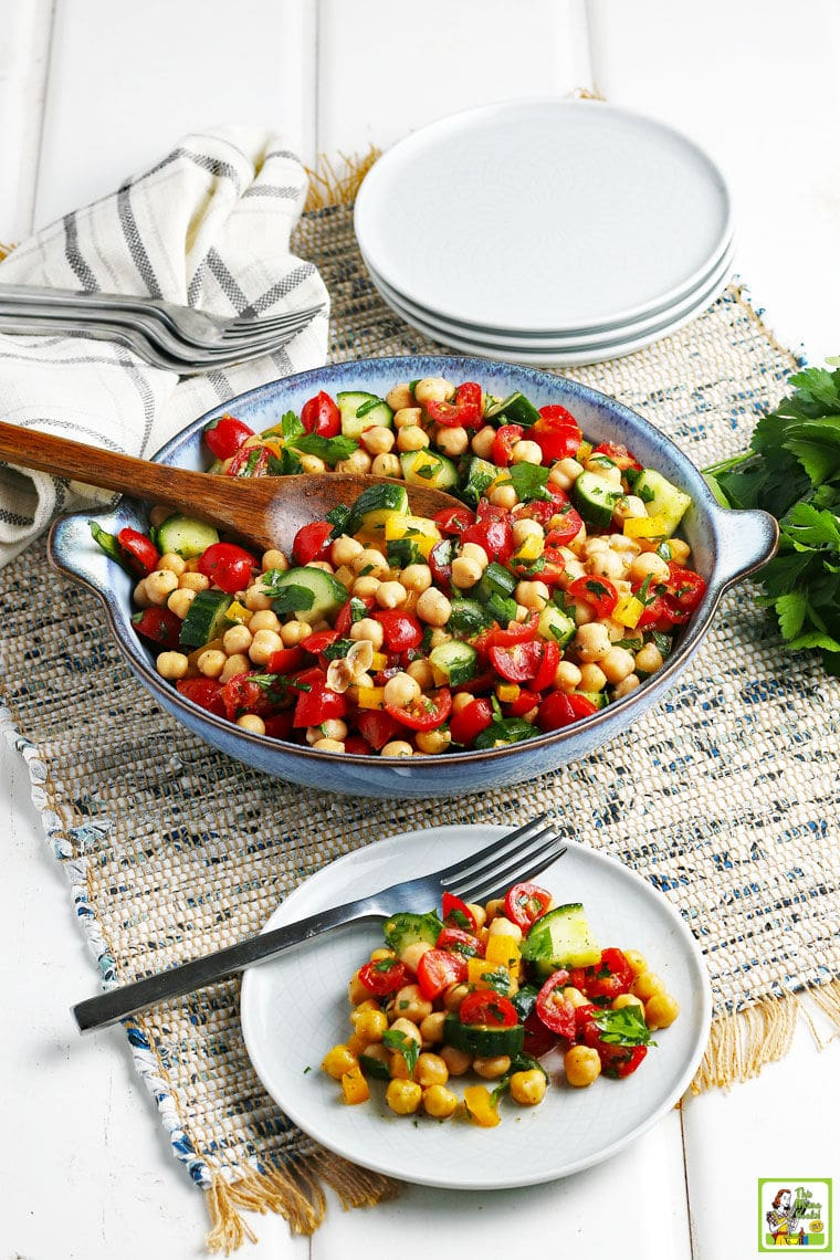 Overhead shot of a blue bowl and white plate with fork with garbanzo bean salad on a rustic grey woven placemat with white plates and forks in the background.
