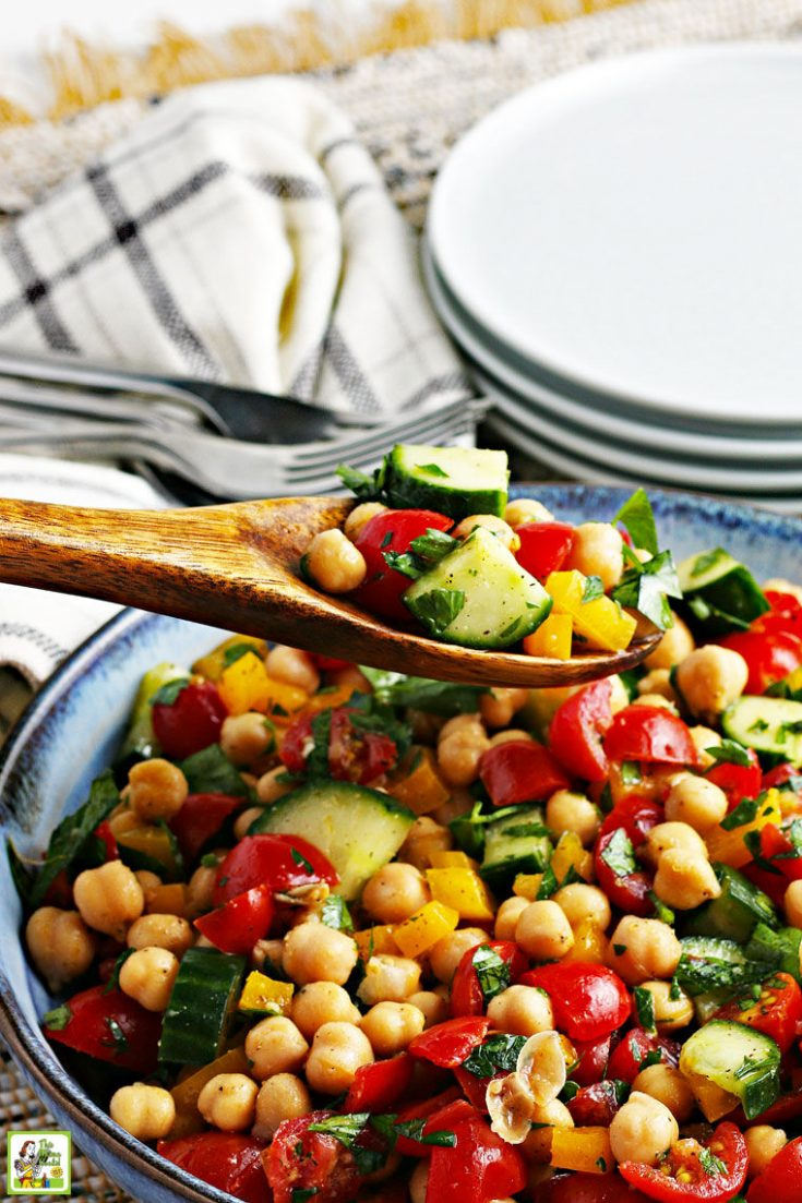 Closeup of a bowl of chickpea salad with cucumbers and tomatoes being served with a wooden spoon with white plates, forks, and white napkins in the background.