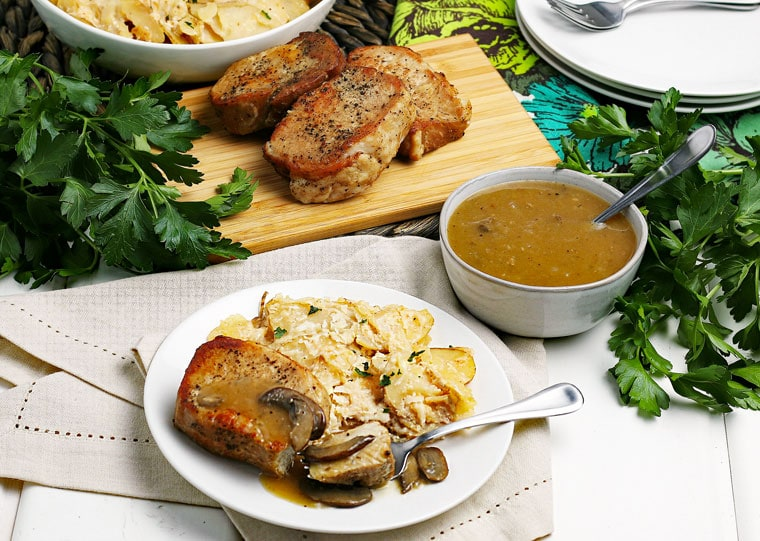 A plate of Instant Pot Pork Chops with a bowl of gravy and more chops on a wooden cutting board surrounding by herbs, napkins, and more plates.